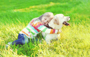little girl hugging dog in grass